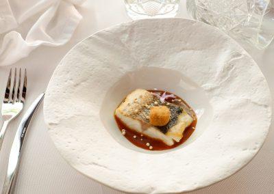 Lubina de esteros Veta la Palma, jugo del menudo, su croqueta y quinoa de los palacios suflada