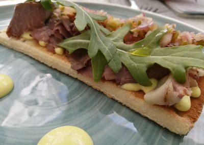Sandwich de pastrami, rúcula, encurtidos y mostaza